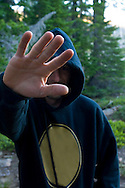 Man in hood sweatshirt holding out arm and hand not wanting picture taken, somewhere in the woods, California