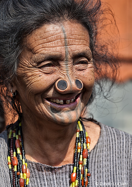 """An elder Apatani woman in Hari village. According to """"Wikipedia"""" - Apatani ladies tend to tattoo their faces thereby spoiling their beauty. The faces of Apatani especially were tattooed in order to spoil their beauty so that males of other neighbouring communities may not take them away. In short, the Apa Tanii used tattoos, ear and nose plugs and Rutting Yarang to buttress their psychological needs to face the inhospitable environments surrounding them in early days. And indeed, it has done well in overcoming adverse environment and survives till date. Younger members of this community have stopped this traditional practice."""