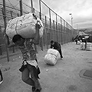 MELILLA, SPAIN - APRIL 21, 2010 : The border of El Barrio Chino is located next to the separation fence between Spain and Morocco and at the end  of a ramp by the which the porters  have to push or carry contraband packages that weigh 80 to 100 kg. on April 21 , 2010 in Melilla. Spain. Every day at the pedestrian border of El Barrio Chino hundreds of people are involved in transporting smuggled goods from Melilla a Spanish enclave on the North African coast to Morocco.For each package introduced in morocco receive between 3 an 5 euros depending on size,with a little luck achieved make three trips a day.It is estimated that from Monday to Thursday on foot enter Melilla 8.000 porters, mostly women, to return to Morocco with huge sacks of goods from the warehouse border area of Beni Enzar in Melilla .( Photo by Jordi Cami  )