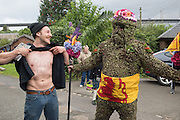 WOJTEK GASIOROWSKI; SHOWING HIS BURRY MAN TATTOO BURRYMAN ANDREW TAYLOR, Burry Man, Queensferry. 12 August 2016 Alocal man is covered from head to ankles in burrs and paraded a 7 mile route around the town visiting the community.<br /> Tradition holds that he will bring good luck to the town if they give him whisky and money,  This year he wore a Scottish flag.