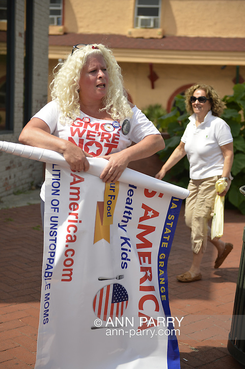 Huntington, New York, U.S. - August 6, 2014 - A protestor from Moms Across America, a national coalition of Unstoppable Moms against GMO, genetically modified organisms, is rolling up her banner near the book signing for H. Clinton's new memoir, Hard Choices, at Book Revue in Huntington, Long Island, during a nationwide tour.
