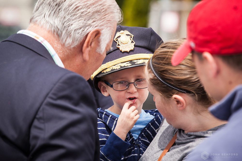 Manchester, NH, mayor Ted Gatsas (l) greets a boy wearing a police officer's hat at the reveal ceremony for the 2016 Building on Hope project at the Michael Briggs Community Center / Manchester Police Athletic League in Manchester, NH.