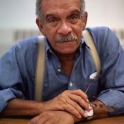 Derek Walcott was a poet and playwright. He won the Nobel Prize for Literature in 1992. Originally from St. Lucia, Walcott spent much of his life in New York City. This photograph was taken in his office as a visiting professor at NYU in 2002.