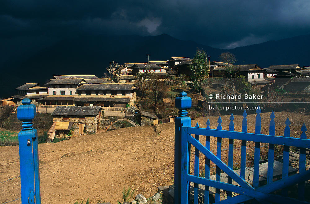 Under a threatening sky, freshly-painted blue gates overlook the Himalayan village of Ghandrung bathed in sunshine in central Nepal. Also called Ghandruk or Gandruk, this settlement is situated in what is known as the Annapurna Sanctuary (conservation region), a 55-km-long massif whose highest point, Annapurna I, stands at 8,091 m (26,538 ft), making it the 10th-highest summit in the world. The village is also a stopping-off point for trekkers and backpackers who pass-by on their way to the walk in high peaks. The Mountain Region (Parbat in the Nepali language) is situated at 4,000 meters or more above sea level. Houses and dwellings are substantial structures with properties well-swept and well-maintained.