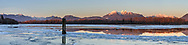 Panorama of the Fraser River almost covered in ice during a rare winter cold snap.  Various mountains of the Pacific Coast Ranges are shown including Coquitlam Mountain, Burke Mountain, Gwendoline Peak, Mount Blanshard (Golden Ears) and Mount Robie Reid.  Photographed from Tavistock Point at Brae Island Regional Park in Langley, British Columbia, Canada.