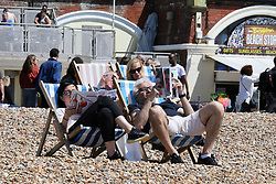 © Licensed to London News Pictures. 30/05/2021. Brighton, UK. Sun-seekers on deck-chairs on the Brighton seafront on the hottest day of the year so far. According to the Met Office, a high of 24 degrees celsius is forecast for the bank holiday weekend, after weeks of rain in the South East of England. Photo credit: Dinendra Haria/LNP