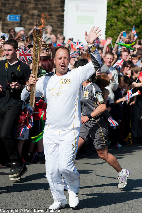 Olympic Torch reaches Sheffield Chapeltown/Ecclesfield/Parson Cross leg.<br /> Bearer 103 Christopher Godwin carries the torch out of chapeltown and on p Ecclesfield Road<br /> 25 June 2012.Image © Paul David Drabble