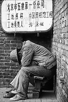 Exhausted workers sleeping during a break. Beijing, China.