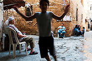 Sidon, Lebanon - September 24, 2010: A boy leaps in front of a camera as neighbors sit outside and visit in the old city of Sidon.