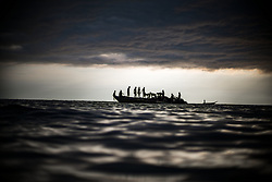 TANZANIA. LAKE TANGANYIKA. OCTOBER 2016. Fishermen off the coast of Kazinga. The men standing on the smaller boats are spotters for the larger boats. Once the small fish, mostly Dagaa, is spotted the large boats with nets and many fishermen arrive for the catch. Kazinga was founded in 1957. An old man started it, his name was Anzuruni and nobody was there before him. Kazinga means a place where there is fishing, a certain type of fishing using a jig. They then used small boats with lanterns and tied a net on the boat. As the population increased, bigger boats became necessary to catch more fish. One of their current forms of fishing, with groups and nets and engines, they began in 1980. It is called ring net fishing. Spotters in small boats look mostly for dagaa and there is no set way to do it. At night, they use other boats and mostly catch dagaa and mikabuka and others. The kids on the boat, when they become 4 or 5 they may begin riding along in the boat, helping to scare fish into the net as well as learning from the older men.<br /> <br /> BIO: Raised in the Skagit Valley, a farming community in Washington State, Michael became known for his documentation of the Libyan Revolution and the resulting monograph, Libyan Sugar (2016), which won the 2016 Paris Photo-Aperture Foundation First Photo-book award and the 2017 International Center of Photography Infinity Artist Book award. Yo Soy Fidel (2018), his book documenting Cubans observing Fidel Castro's 2016 funeral procession, was exhibited during the 2018 Recontres d'Arles. Previously a photographer with Magnum Photos, Michael is a contributing photographer at National Geographic, The New York Times Magazine, Time and other editorials. Commercial clients include Chopard, Land Rover, Nike, Sony, Amnesty International, Hyperice, HBO, Tecno and Al-Jazeera. He is based in Los Angeles. <br /> <br /> WEBSITE: michaelchristopherbrown.com<br /> INSTAGRAM: @michaelchristopherbrown
