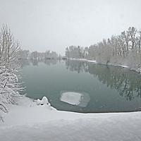 Snow falls over a pond near Bozeman, Montana.