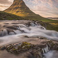 A golden glow falls on Kirkjufell, a mountain situated on Iceland's Snæfellsnes peninsula.