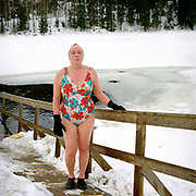 Portrait of a women in a flowery swimming costume standing on the path down to the hole in the ice on the small lake Vuorilampi, Jyvaskyla, Central Finland. Ice swimming takes place in a body of water with a frozen crust of ice, which requires a hole cutting in it.  In Finland, the ice swimming tradition has generally been connected with the sauna tradition and it is not seen as an ascetic or religious ritual, but as a way to cool off rapidly after staying in the sauna and as a stress relief.