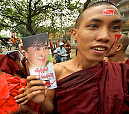 A sweating monk shows a leaflet of Aung San Suu Kyi propaganda to manifest his support to the NLD at the upcoming elections. Mandalay, Myanmar, 2012