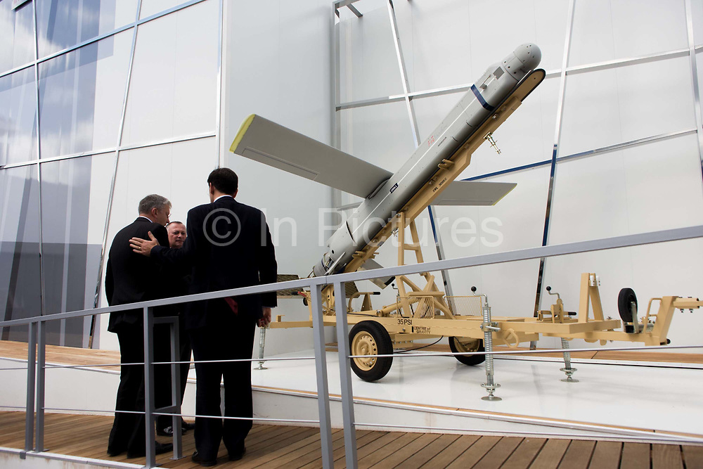 Businessmen inspect the 12ft Fire Shadow missile on manufacturer MBDA's trade stand at the Farnborough airshow. An employee shows visiting guests to this exhibit the merits of its use and design. The so-called lurker bomb is designed to loiter above a battlefield for up to 6 hours before attacking stationary or mobile targets and also able to shadow British troops for up to ten hours or 100 miles, ready to take out enemy targets with surgical precision at a minute's notice. . The Farnborough International Airshow is a seven-day international trade fair for the aerospace industry and held every two years in mid-July at Farnborough Airport in Hampshire, England known as the home of British aviation, held since there since 1948. The show is usually attended by more than 1,300 exhibitors and 150,000 trade visitors.