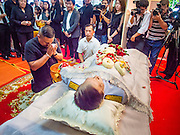 12 OCTOBER 2104 - BANG BUA THONG, NONTHABURI, THAILAND: JATUPORN PROMPAN, a prominent Red Shirt leader, prays at the body of Apiwan Wiriyachai on the first day of Apiwan's funeral rites at Wat Bang Phai in Bang Bua Thong, a Bangkok suburb, Sunday. Apiwan was a prominent Red Shirt leader, member of the Pheu Thai Party of former Prime Minister Yingluck Shinawatra, and a member of the Thai parliament. The military government that deposed the elected government in May, 2014, charged Apiwan with Lese Majeste for allegedly insulting the Thai Monarchy. Rather than face the charges, Apiwan fled Thailand to the Philippines. He died of a lung infection in the Philippines on Oct. 6. The military government gave his family permission to bring him back to Thailand for the funeral. He will be cremated later in October. The first day of the funeral rites Sunday drew tens of thousands of Red Shirts and their supporters, in the first Red Shirt gathering since the coup.    PHOTO BY JACK KURTZ