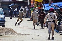 April 27, 2018 - Srinagar, J&K, India - Indian government forces chase Kashmiri protesters during clashes after the friday prayers  in Srinagar, Indian administered Kashmir. Clashes erupted between Kashmiri protesters and Indian paramilitary forces after Friday congregation prayers near Kashmir's historic Grand Mosque or Jamia Masjid in old city of Srinagar. The stone throwing protesters were protesting against Indian rule. (Credit Image: © Saqib Majeed/SOPA Images via ZUMA Wire)