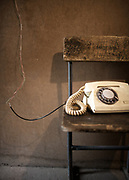Old phone on a chair. Road Police office. <br /> Near Khorog.<br /> <br /> The town of Khorog (2200m), is the capital of the Gorno-Badakhshan Autonomous Province (GBAO) in Tajikistan. It is situated in the Pamir Mountains (ancient Mount Imeon) at the confluence of the Gunt and Panj rivers.<br /> The city is bounded to the south and to the north by the deltas of the Shakhdara and Gunt rivers, respectively. The two rivers merge in the eastern part of the city flow through the city, dividing it almost evenly until its delta in the river Panj, also being known as Amu Darya, or in antiquity the Oxus on the border with Afghanistan. Khorog is known for its beautiful poplar trees that dominate the flora of the city.<br /> Khorog is one of the poorest areas of Tajikistan, with the charitable organization Aga Khan Foundation providing almost the only source of cash income. Most of its inhabitants are Ismaili Muslims.<br /> <br /> Tajikistan, a mountainous landlocked country in Central Asia. Afghanistan borders it to the south, Uzbekistan to the west, Kyrgyzstan to the north, and People's Republic of China to the east. Tajikistan also lies adjacent to Pakistan separated by the narrow Wakhan Corridor.<br /> Tajikistan became a republic of the Soviet Union in the 20th century, known as the Tajik Soviet Socialist Republic.<br /> It was the first of the Central Asian republic to gain independence in December 1991.