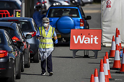 © Licensed to London News Pictures. 17/09/2020. WATFORD, UK.  An NHS worker prepares to check in a car driver ahead of their test at the Covid-19 testing centre outside Watford General Hospital in Hertfordshire.  It is reported that the increased demand for Covid-19 tests has led to local shortages of testing slots and access to community testing has had to be rationed because labs are struggling to keep up with demand.  Photo credit: Stephen Chung/LNP
