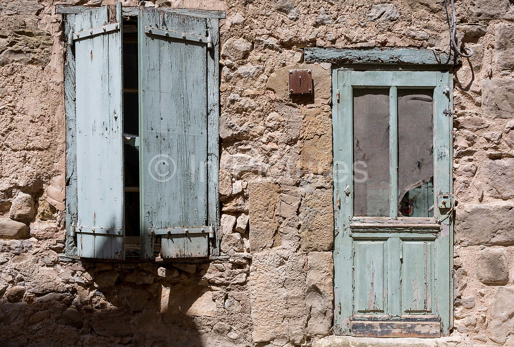 In afternoon heat, baked hard paint textures on village closed wooden shutters and doorway, on 26th May, 2017, in Villerouge-Termenes, Languedoc-Rousillon, south of France.