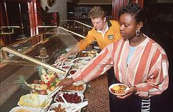 Man and woman at selfservice salad bar,