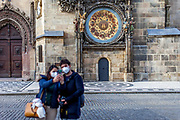 A couple doing a selfportrait infront of the Astronomical clock at Old Town Square in Prague. As of 21st of October 2020 people have to wear face masks outside and inside except while doing physical activities as running or cycling.
