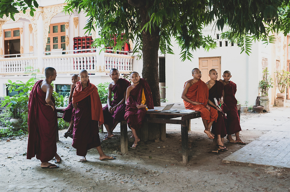 Mandalay, Myanmar - November 10, 2011: Buddhist monks or novices, several with school books, at a monastery in Mandalay.