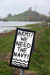 """© London News Pictures. 31/01/2014. Burrowbridge, UK. A sign reading """"ARM? WE NEED THE NAVY!"""" near flood water in  Burrowbridge, Somerset on the Somerset levels. The ruin of St Michaels church on the top of Burrow Mump can be seen in the background. The area has been hit severely by recent flooding which is forecast to get worse over the weekend . Photo credit: Jason Bryant/LNP"""