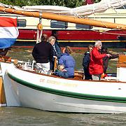 NLD/Muiden/20050514 - Koninging Beatrix komt terug van een dagje zeilen op de Groene Draeck met vrienden in de haven van Muiden, Beatrix aan het roer