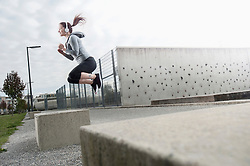 Young woman jumping on a concrete block and listening to music, Bavaria, Germany