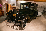 "Trapper George Johnston bought his dream car in 1928, a four cylinder Model AB Chevrolet sedan, shipped by steamer from Whitehorse several hundred miles via the Yukon and Teslin Rivers to Teslin village. The local Taylor & Drury store fueled it with naphtha. At first, his only road was 78 miles of frozen Taslin Lake. For his taxi service in Teslin, George Johnston built a 3- to 5-mile road, which later became part of the Alaska Highway. The car is now displayed in the George Johnston Museum, Alaska Highway, Teslin, Yukon, Canada. The Alaska Highway was built as a military road during World War II in just 9 months in 1942, to link existing airfields via Canada to the territory of Alaska. The ALCAN Highway (a military acronym for Alaska-Canada) opened to the public in 1948. It begins in Dawson Creek, British Columbia, and runs via Whitehorse, Yukon to Delta Junction, Alaska. The ""Alaskan Highway"" is comprised of British Columbia Highway 97, Yukon Highway 1 and Alaska Route 2. While the ALCAN measured 2700 kilometers (1700 mi) upon completion in 1942, by 2012 it was rerouted and shortened to 2232 km (1387 mi). Once legendary for being a rough, challenging drive, the highway is now paved over its entire length. Delta Junction, at the end of the highway, claims ""Historic Milepost 1422"" where the Alaska Highway meets the Richardson Highway, which continues 96 mi (155 km) to the city of Fairbanks at Historic Milepost 1520, often (but unofficially) regarded as the northern portion of the Alaska Highway (although its Mileposts are measured from Valdez)."