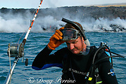 diver and underwater lava sculptor Bud Turpin dons gear <br /> and prepares to enter the water as hot lava from Kilauea <br /> Volcano pours into the ocean behind him, Hawaii Island <br /> (the Big Island ), Hawaii, U.S.A. (central Pacific)  MR 318