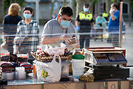 A client, wearing a protective face mask, prepares to pay for his purchase at a stall in the outdor market. Irun (Basque Country). May 09, 2020. As the downscaling progresses, there are more and more businesses and commercial activities that take over their activity, after having been closed due to the blockade ordered by the Spanish government to prevent the spread of the COVID-19. (Gari Garaialde / Bostok Photo)