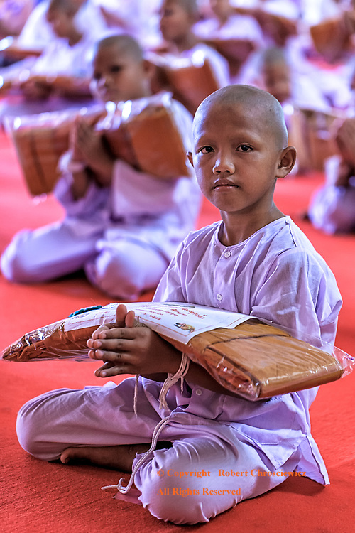 Novice Monks: Rows of young boys kneel in prayer wearing white robes and each holds his new saffron robes as he starts the ordination ceremony to become a novice monk, Phra Mahathat Wat Nong Wang, Khon Kaen Thailand.