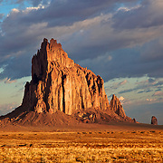 """Shiprock (Navajo: Tsé Bit'a'í, """"rock with wings"""" or """"winged rock"""") is a rock formation rising nearly 1,583 feet  above the high-desert plain on the Navajo Nation in San Juan County, New Mexico."""