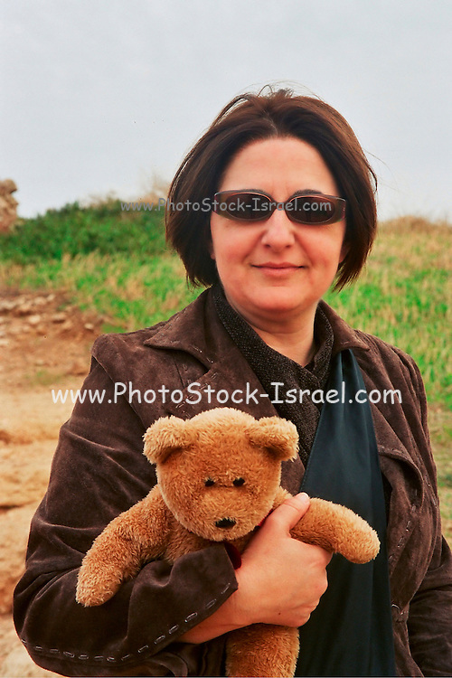 woman, 30 to 40 holding a teddy bear on a winter day