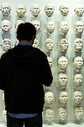 Visitor views Wall of Nias Islanders facial casts in 20th Century Gallery at Rijksmuseum, Amsterdam, Holland