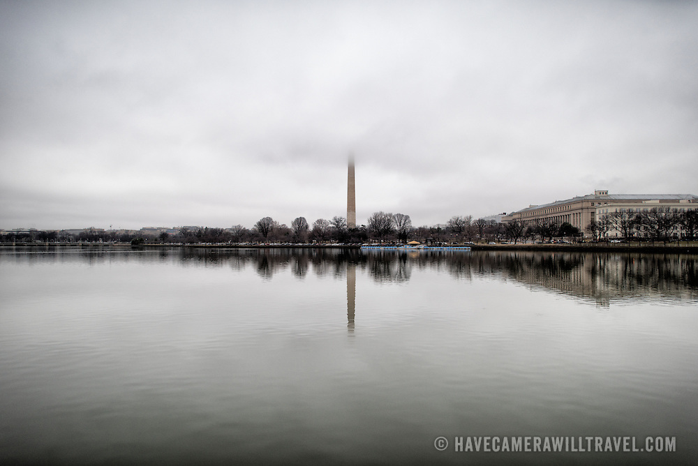 The top of the Washington Monument disappears into low clouds, as seen from across the Tidal Basin in Washington DC.