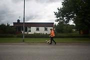 A lady walks her poodle in Kosta, Sweden, 5th of August 2016. Kosta is a small town in the Southern part of Sweden surrounded by large forests of pine trees.