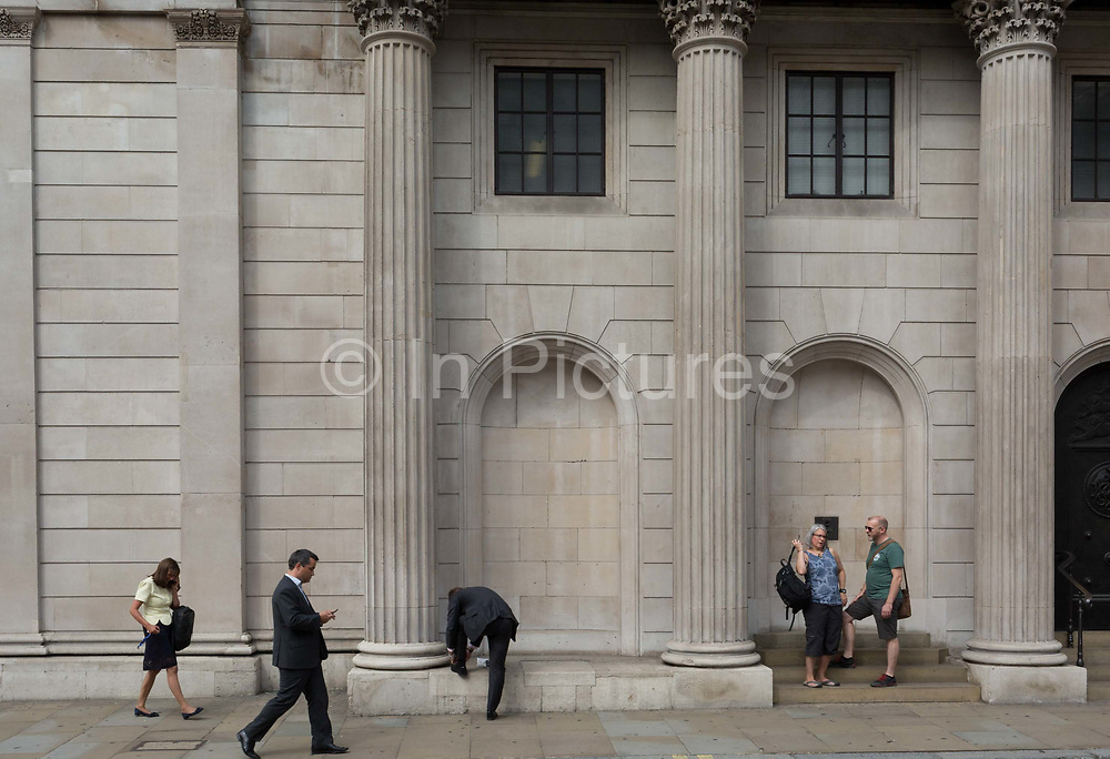 Londoners walk, tie a loose lace and stand beneath the columns and pillars of the Bank of England on Threadneedle Street in the City of London - the capitals financial district, on 3rd September 2018, in London England. The Bank of England, is the central bank of the United Kingdom and the model on which most modern central banks have been based. Established in 1694, it is the second oldest central bank in the world. Sir Herbert Bakers rebuilding of the Bank, demolishing most of Sir John Soanes earlier building, was described by architectural historian Nikolaus Pevsner as the greatest architectural crime, in the City of London, of the twentieth century.