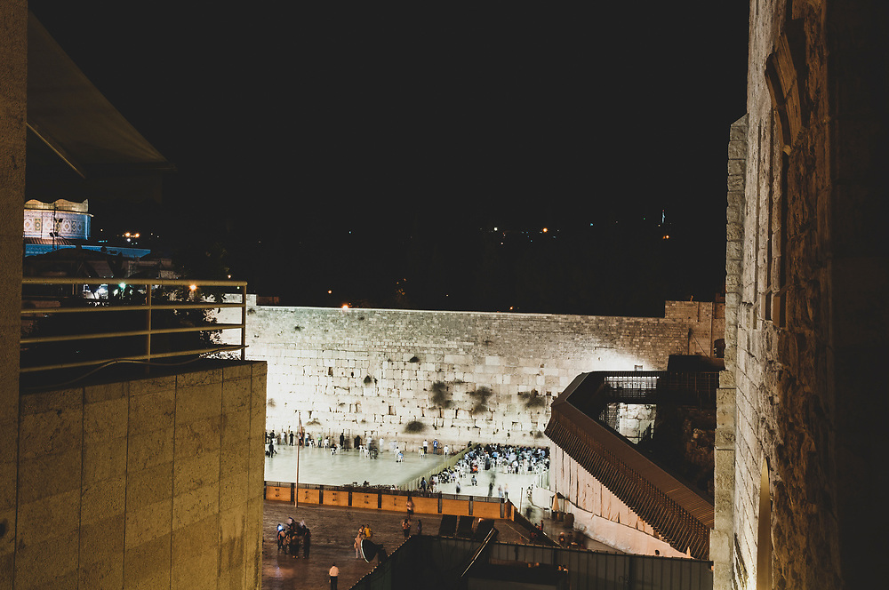 View of the illuminated Western Wall, or Wailing Wall, In Jerusalem's old city at night. A portion of the Dome of the Rock is visible on the left.