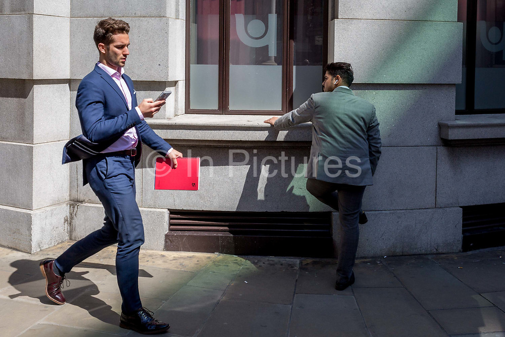 A businessman faces the wall of an office building wall in the City of London, the capitals ancient, financial district, on 14th May, in London, England.