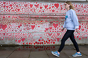 A woman walks past the National Covid memorial wall, a sea of red love hearts remembering all those who have died due to the COVID-19 pandemic on the 25th of May 2021 on the south bank in London, United Kingdom. Over 150,000 people have lost their lives in the United Kingdom due to the pandemic, the wall is a space for them to be remembered.