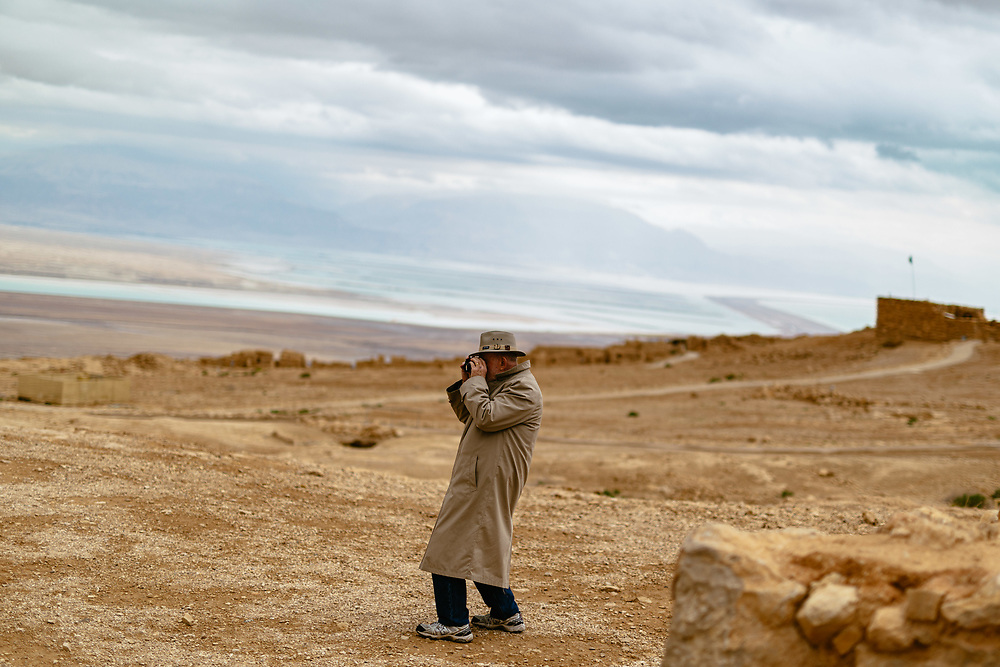 An American Evangelical Christian tourist, part of a group led by Former Arkansas governor Mike Huckabee (not pictured), uses his binoculars during a visit to the ancient hilltop fortress of Masada in the Judean desert in Israel, on February 19, 2015. The ancient ruined desert fortress on a wind-swept plateau overlooking the Dead Sea is seen by many as an emblem of Israel's fighting spirit, it is believed to be the place where close to a thousand Jewish rebels killed themselves and each other about two millennia ago, rather than surrender and fall into slavery under the Romans.