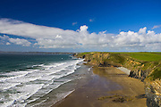 Two people walk on almost deserted DruidstoneBeach near Broad Haven, Pembrokeshire, Wales