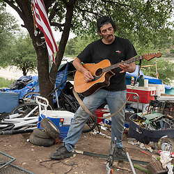 Musician and handyman Douglas Crawford strums his guitar for spare change near his camp at the corner of Ben White Blvd. and south Congress Avenue in Austin, TX where he's lived for over a year. Crawford, 60, says he stays to himself and isn't worried about Austin's new homeless crackdown and camping ban starting Tuesday.