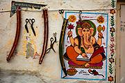 Ganesh the elephant-headed Hindu god of beginnings overlooks a knife sharpening stall on 29th January 2018  in Jaisalmer, Rajasthan, India.