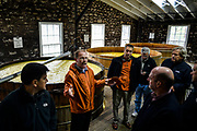 30166675A VERSAILLES, Ky. - Nov. 7, 2014 - Woodford Reserve Distilleries Master Distiller Chris Morris (second from left) gives a private tour as bourbon goes through the distilling process behind him.<br /> <br /> William DeShazer for the New York Times