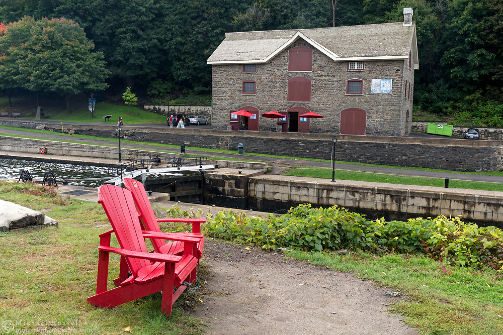 Two Adirondack chairs next to the Rideau Canal (Ottawa Locks 1-8) and the Bytown Museum in Ottawa, Ontario, Canada. The Bytown Museum is housed in the Commissariat Building - the oldest stone building in Ottawa which was built in 1827.  The Commissariat Building was used as a storehouse, office and treasury during the construction of the Rideau Canal during 1826-1832).