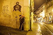 A couple kisses on a street in Alfama district in Lisbon.